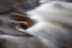 Soft flowing water over a well worn brown stone Royalty Free Stock Photos
