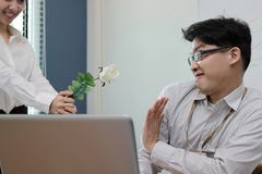 Soft focus angry Asian business man refuses a white roses from attractive woman. Disappointed love concept. Soft focus angry Asian business men refuses a white stock photography