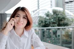 Soft focus of attractive young Asian business woman talking on phone in office with copy space background. Stock Photos