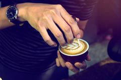 Soft focus at Barista performing skill of pouring latte art in wing tulip pattern by using handleless pitcher. Selective focus on. Barista hand pouring latte Stock Photos