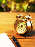 Soft focus of blank notebook with vintage alarm clock and black pen on wood table. The background is green from tree and light bokeh Royalty Free Stock Photos