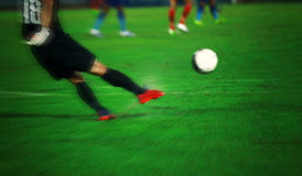 Soft focus and blurry of goalkeeper knocks and kicking the ball. Soft focus and blurry of Soccer player kicking ball in action at stadium Stock Images