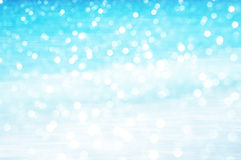 Soft focus bokeh light effects over a rippled, blue water Stock Photos