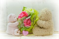 Soft focus couple of cute bears holding roses bouquet Stock Photos