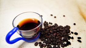 Soft focus of a cup of energetic drink infusion and coffee beans with a raw background. for detox and healthy concept royalty free stock photography