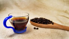 Soft focus of a cup of energetic drink infusion and coffee beans on a wooden spoon with a raw background. for detox and healthy co. Ncept stock photography