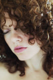 Soft focus face of curly haired brunette stock image