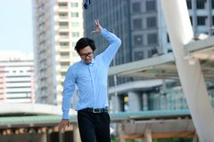 Soft focus of frustrated stressed young Asian businessman walking and throwing his necktie in urban building city background. royalty free stock images