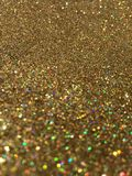 Soft focus gold glitter sparkle background. Close up image of gold glitter with multicolored lights reflecting off the shimmer. Festive holiday sparkle glitter Royalty Free Stock Photos
