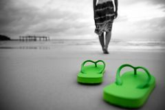 Soft focus on Green flip flop with sad woman walking. On sandy beach. black and white photo royalty free stock image