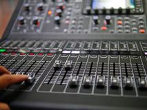 Soft focus hand adjusting professional digital audio mixer controller in the control room, Sound mixer control for live music and. Studio equipment, Quality royalty free stock photography
