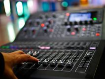 Soft focus hand adjusting professional digital audio mixer controller in the control room, Sound mixer control for live music and. Studio equipment, Quality stock image