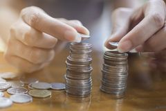 Soft focus of hand of Asian woman putting a silver coin on top of two pile for stacking. On the wooden table Stock Images