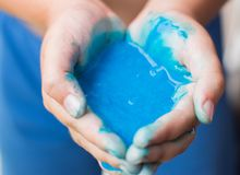 Soft focus of hand holding homemade toy called slime. Soft focus of children hand holding blue homemade toy called slime stock photo
