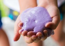 Soft focus of hand holding homemade toy called slime. Soft focus of children hand holding purple homemade toy called slime royalty free stock photography