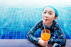 Soft Focus of Happy Children at the Swimming Pool Side, Girl Rel. Axing with Summer Drink, Smile and Looking at Camera, Blue Water as background Royalty Free Stock Images