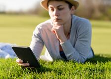 Free Soft Focus Of Woman In Grey Top, Straw Hat  Reading And  Holding Ebook In Her Hands, Lying And Resting On Green Grass On Warm Day Royalty Free Stock Image - 179130886