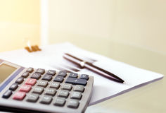 Soft focus of a pen and calculator with paperwork. Stock Photos