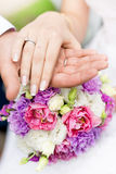 Soft focus photo of groom holding brides hand on bridal bouquet Stock Image