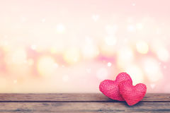 Soft focus red knitted hearts on wooden table with pink bekeh background Stock Image