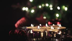 Soft focus shift from star in the back to burning candles in the front. Christmas decoration on dark background with burning candles in front and wooden star in stock video
