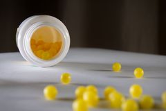 Soft focus shot of small yellow ball pills with attention to the inside of the bottle royalty free stock photo