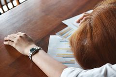 Soft focus of tired overworked young business woman bend down head on charts in office stock photos