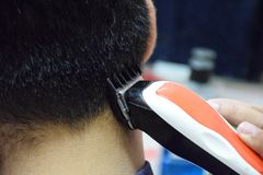 Soft Focus to Men`s hairstyling and haircutting with hair clipper. In a barber shop stock photography