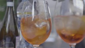 Soft-focus of two glasses of orange drinks. Frame. Fresh summer cocktails stock video