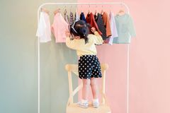 Soft Focus of a Two Years Old Child Choosing her own Dresses fro. M Kids Cloth Rack royalty free stock photography