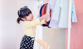 Soft Focus of a Two Years Old Child Choosing her own Dresses fro. M Kids Cloth Rack royalty free stock image