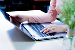Soft focus of woman using laptop, searching, checking, browsing information on the wooden table Royalty Free Stock Photo