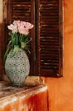A soft focused bouquet of flowers in an old vase on a window sill royalty free stock images
