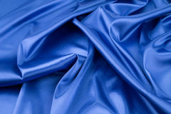 Soft folds of deep blue silk cloth. Royalty Free Stock Images