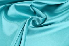 Soft folds and highlights of light blue silk. Royalty Free Stock Photo