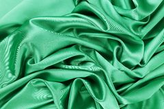 Soft folds and highlights of light green silk. Royalty Free Stock Photography