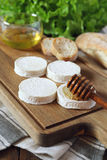 Soft French goat cheese Rocamadour, bread, honey and lettuce Stock Image