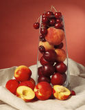 Soft fruits. A collection of plums, peaches and cherries in a glass vase royalty free stock photos