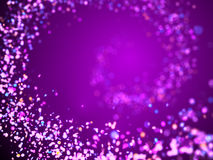 Soft glitter spiral in shades of purple, pink, blue, red and orange in front of a purple background Stock Photos