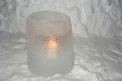 CANDLE GLOW THROUGH ICE LAMP. Soft glow of a burning candle light through a frozen water sculpture Royalty Free Stock Photo