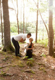 A soft glow in the woods while a couple kiss with pets. A soft summer glow in the woods by a lake, where a men and women hold their dogs and kiss Stock Photo