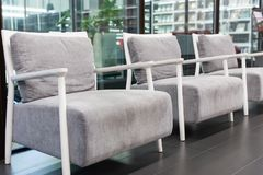 Soft gray fabric armchairs near glass windows Royalty Free Stock Photo