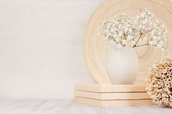 Soft home decor of beige bamboo dish, twigs and white small flowers in ceramic vase  on white wood background. Royalty Free Stock Photos