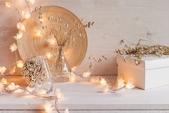 Soft home decor with burning lights on white wooden background. Stock Image