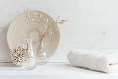 Soft home decor of  glass vase with spikelets and knitted fabric on white wood background. Royalty Free Stock Photo