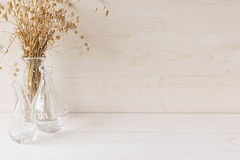 Soft home decor of  glass vase with spikelets on white wood background. Stock Photo