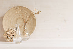 Soft home decor of  glass vase with spikelets and wooden plate on white wood background. Royalty Free Stock Images