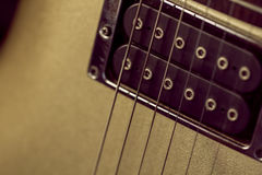 Soft image of a black humbucking pickup on a gold guitar Stock Photography