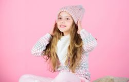 Soft knitted accessory. Tips for caring for knitted garments. Child long hair warm soft woolen hat enjoy softness. Kid. Girl wear knitted soft hat pink royalty free stock photo