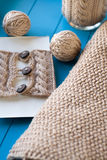 Soft knitted blanket, yarn balls lying on blue background Stock Photo